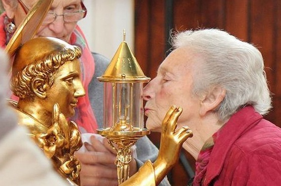 A devouted Roman Catholic kiss the container holding a 750 year old tooth.